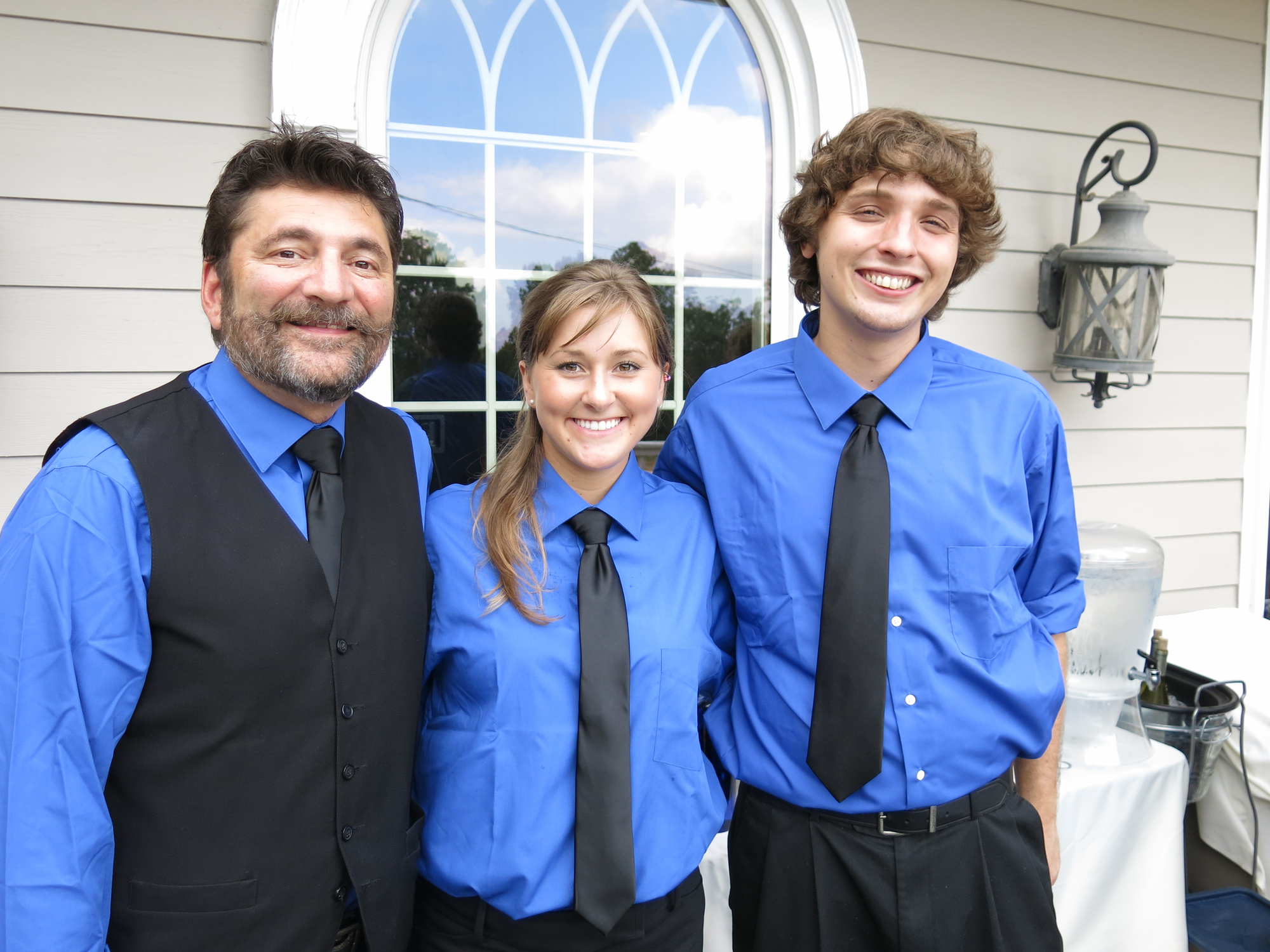 Three employees of Saratoga Event Group and Avenue Catering Concepts, dressed in their uniforms